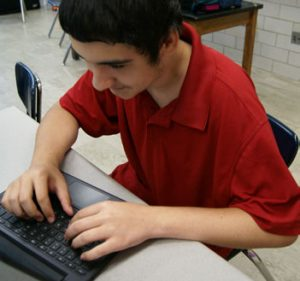 student typing at computer