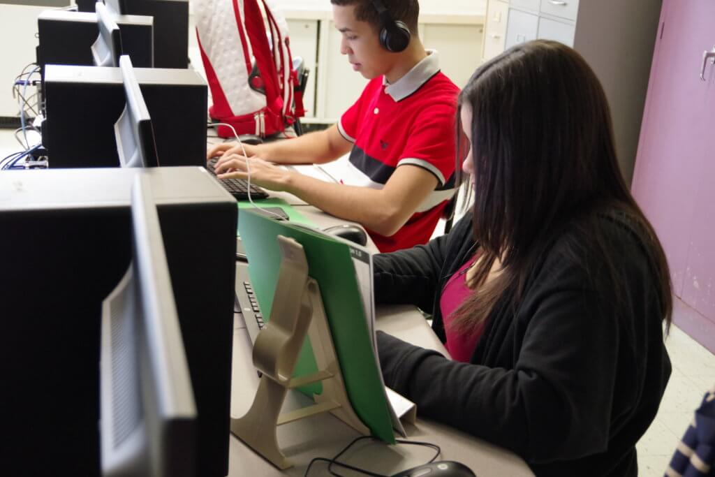 one male and one female student working at computers