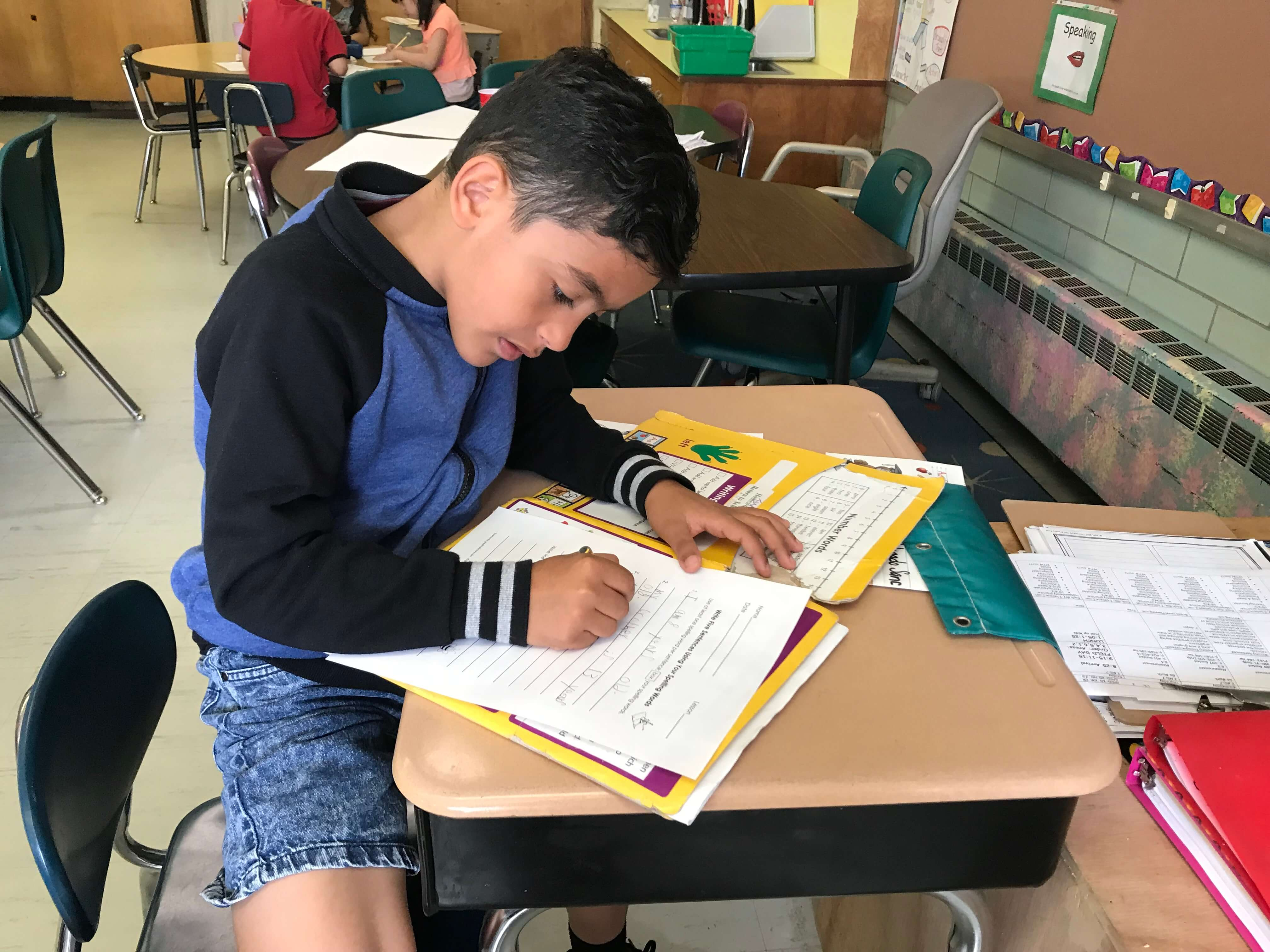 young boy writing in work book on desk, wearing jean shorts and a blue and black shirt