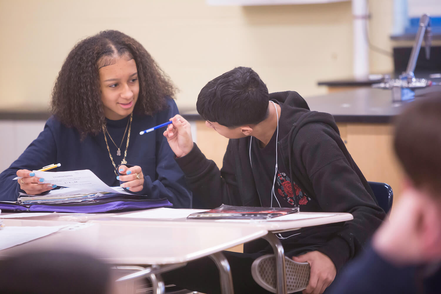 female student with curly hair working with a male student wearing a sweatshirt