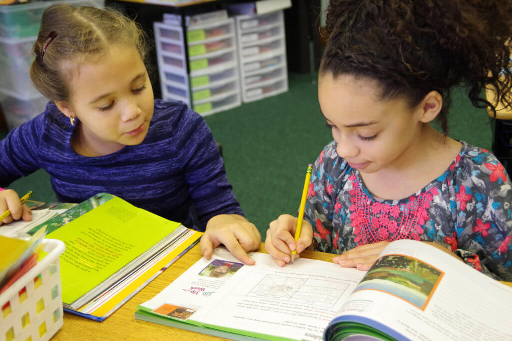 two young female students working together and reading a textbook dual language program metcalf 2018