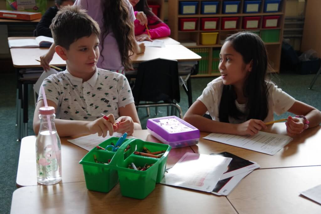 male and female student working at a table at Metcalf School - dual language classroom