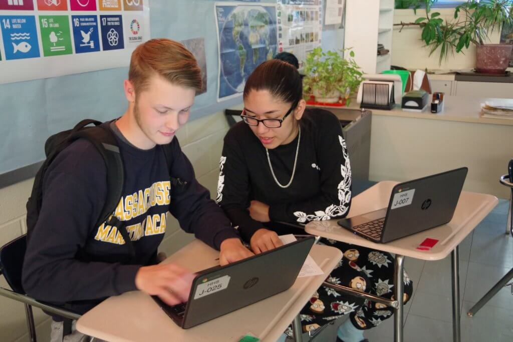 5-16-19 Holyoke Update male high school student in Mass Maritime sweatshirt and female student working together using laptops