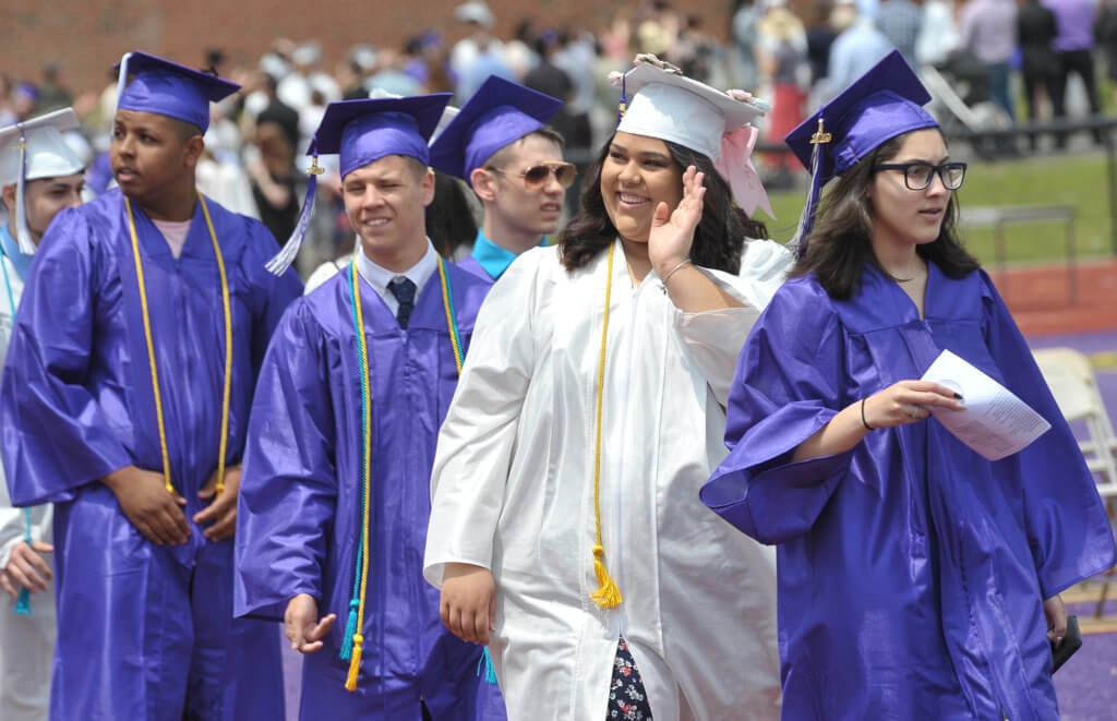 high school graduates in line waving to families