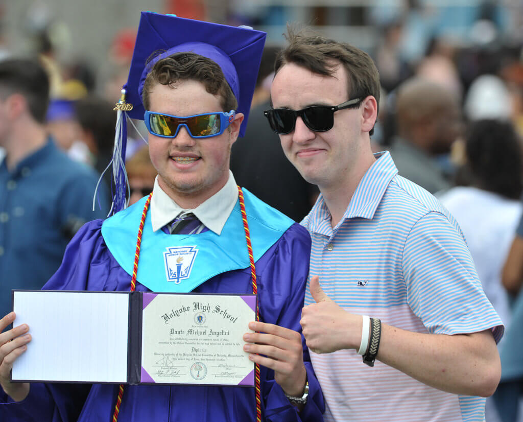 2019 male graduate is holding his diploma and standing with a friend at the commencement ceremony.