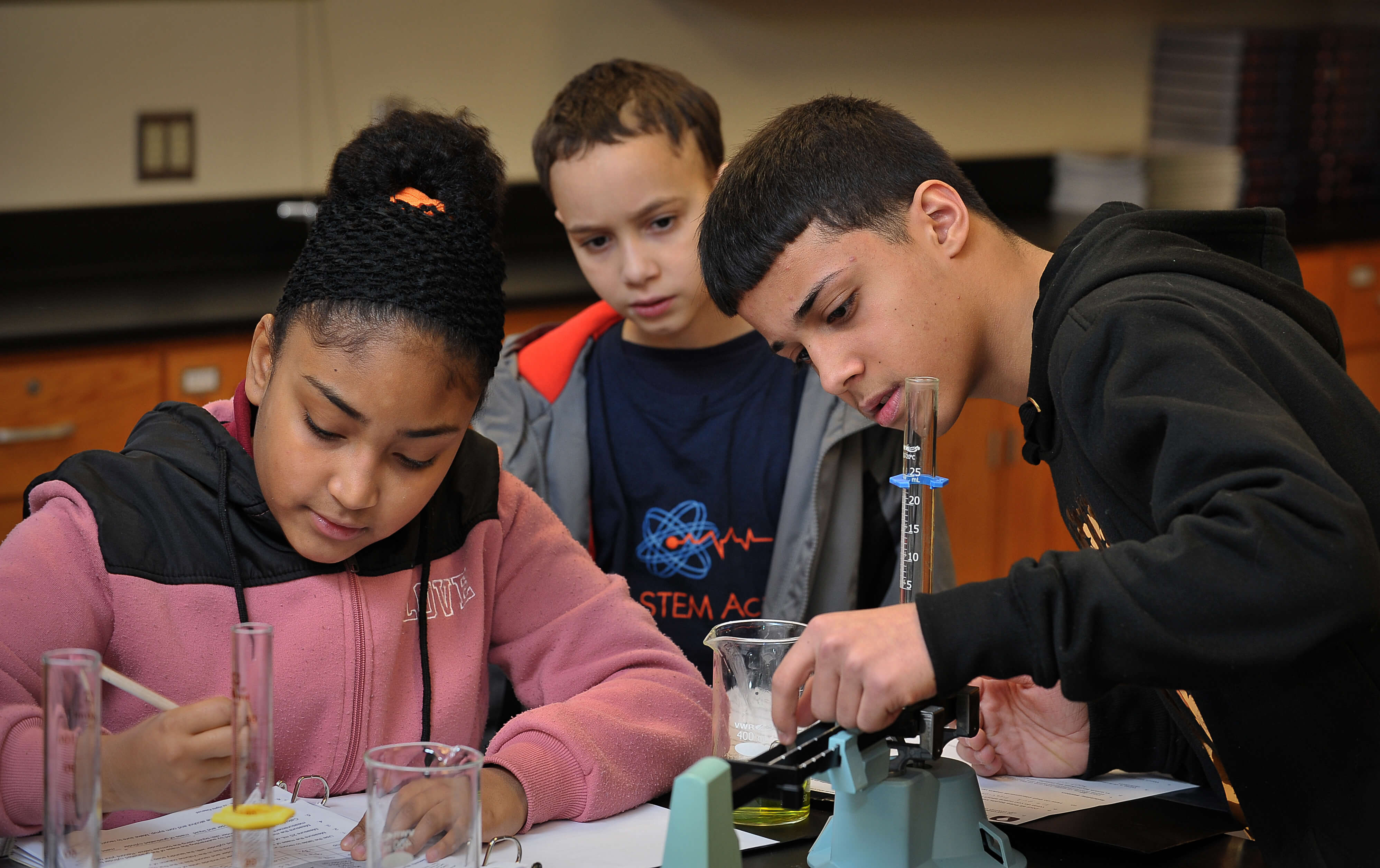 Three students working together with beakers during a science class.