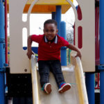 PreK boy playing on the slide during recess at Metcalf School=