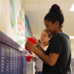 Two female students painting a mural in the halls of HHS North campus.