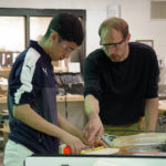 Dean carpentry student conferring with his teacher on a project.