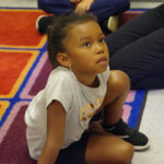 Kelly School kindergarten student sitting during circle time.