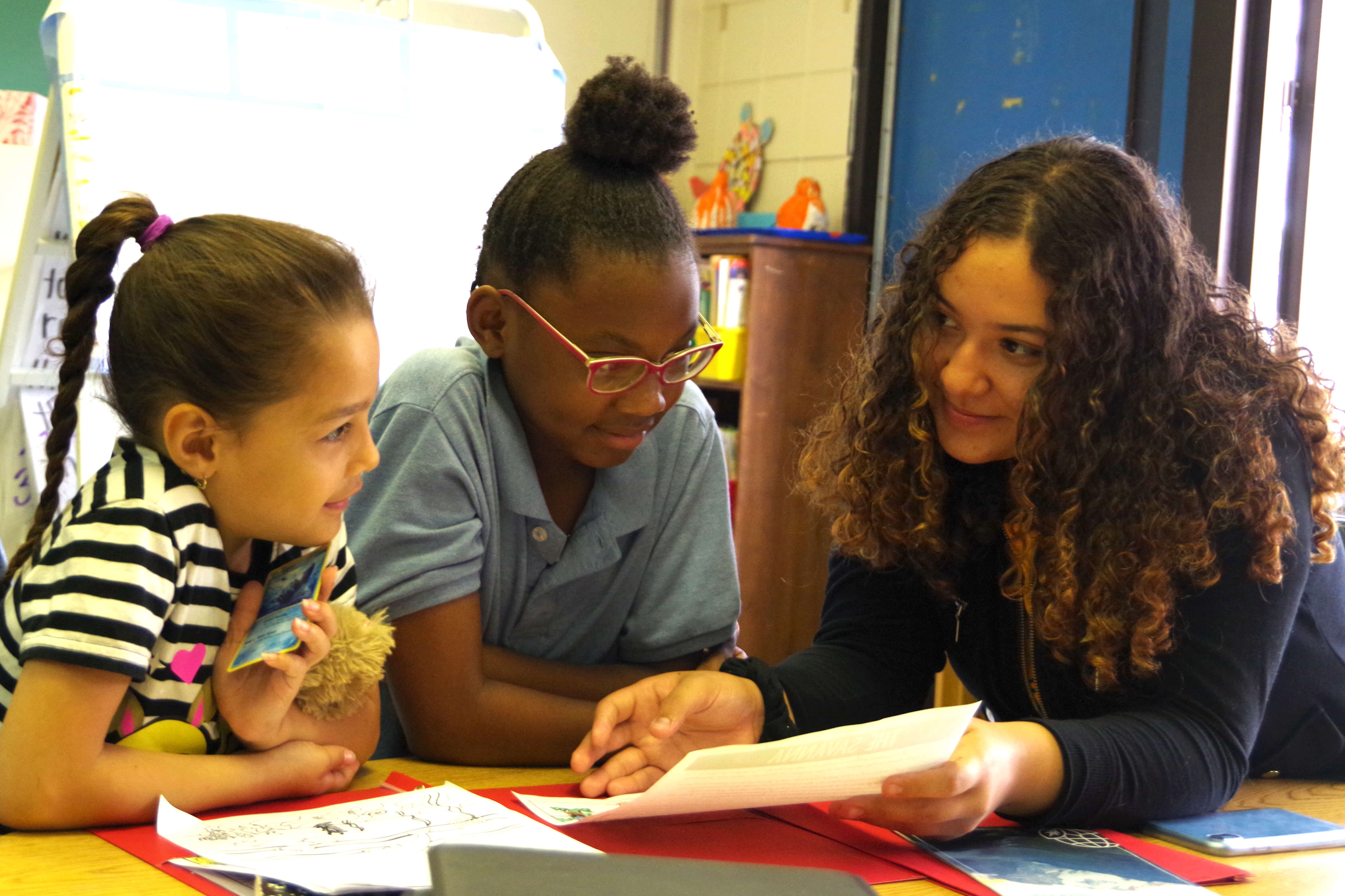 HHS female student mentoring two 2nd grade female students at Kelly School.