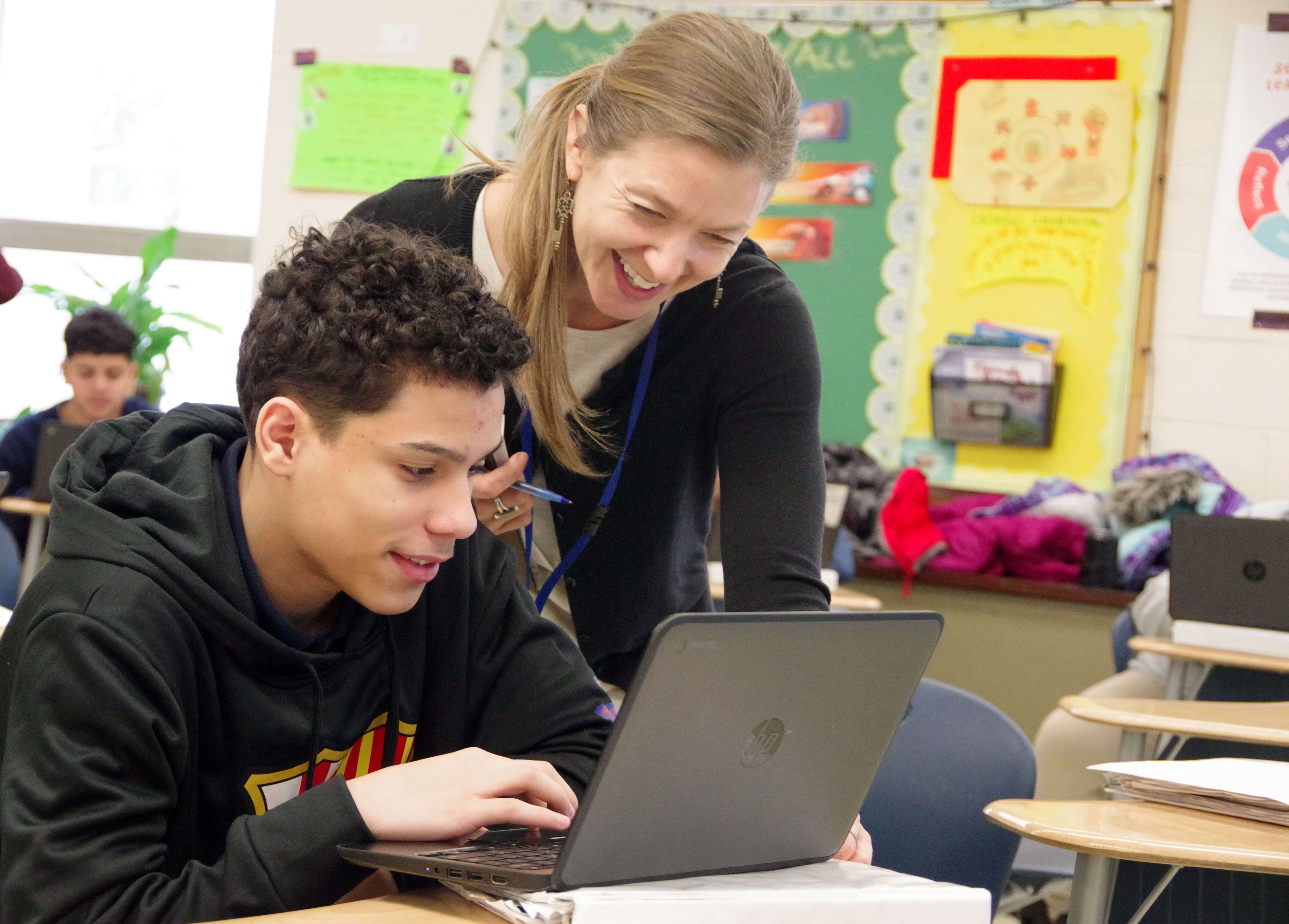 Peck teacher laughing with student working on a laptop