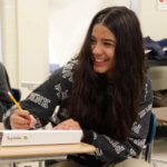 7th grade female student smiling in class at her desk.