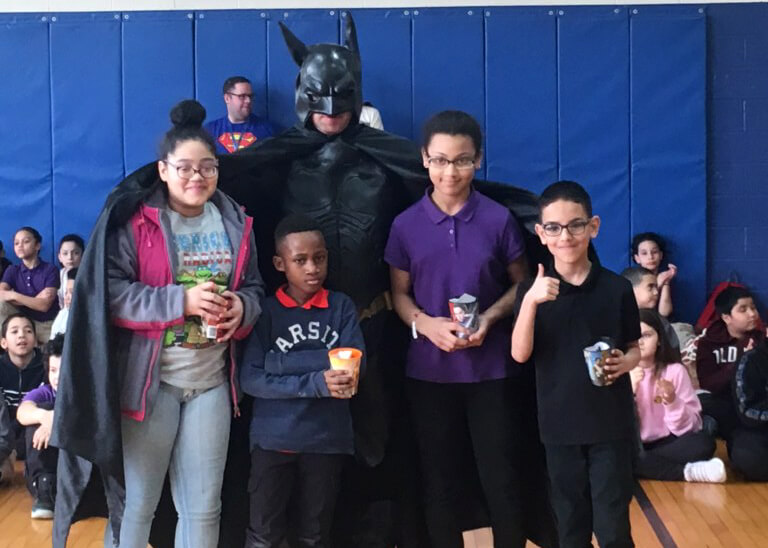 Morgan students posing with Batman as part of their MCAS Superhero celebration.