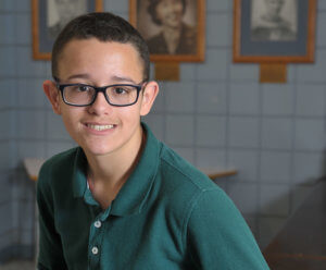 Peck School male student with glasses smiling, wearing a green long sleeved polo shirt 2019 Rising Star