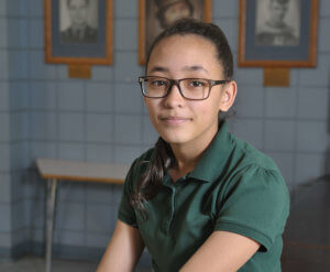Sullivan School female student with glasses smiling, wearing a green polo shirt and khaki pants 2019 Rising Star
