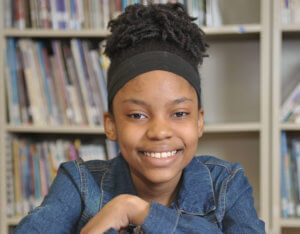 Donahue School female student wearing a jean jacket and headband smiling 2019 Rising Star.