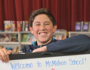 McMahon School male student in gray sweatshirt in front of sign 2019 Rising Star
