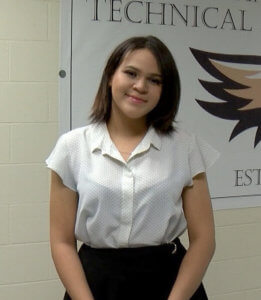 HHS Dean Campus female student smiling in hallway in front of Dean Tech banner, wearing a white blouse and black skirt 2019 Rising Star