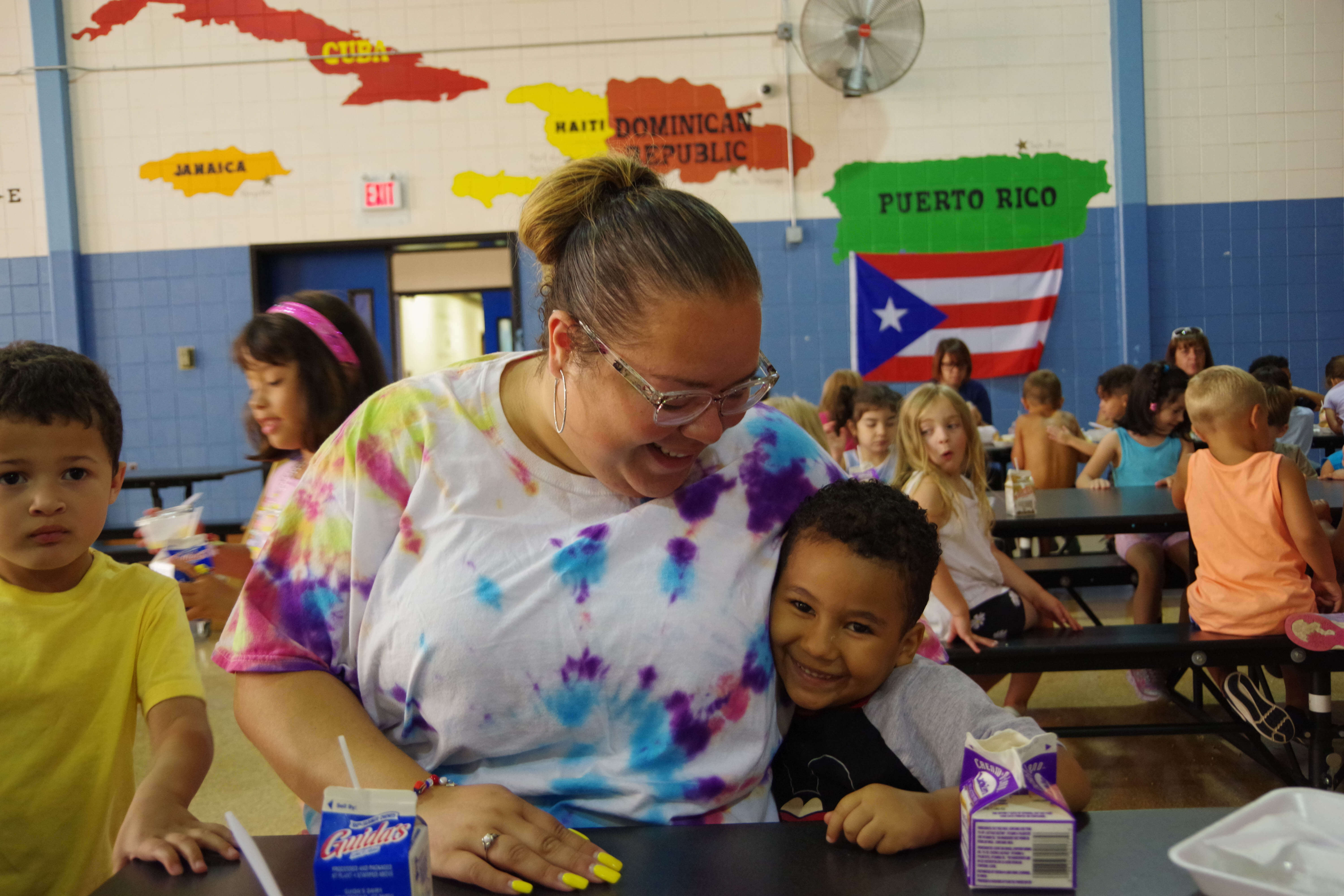 Elementary male student at Donahue in the cafeteria, hugging his teacher during lunch.