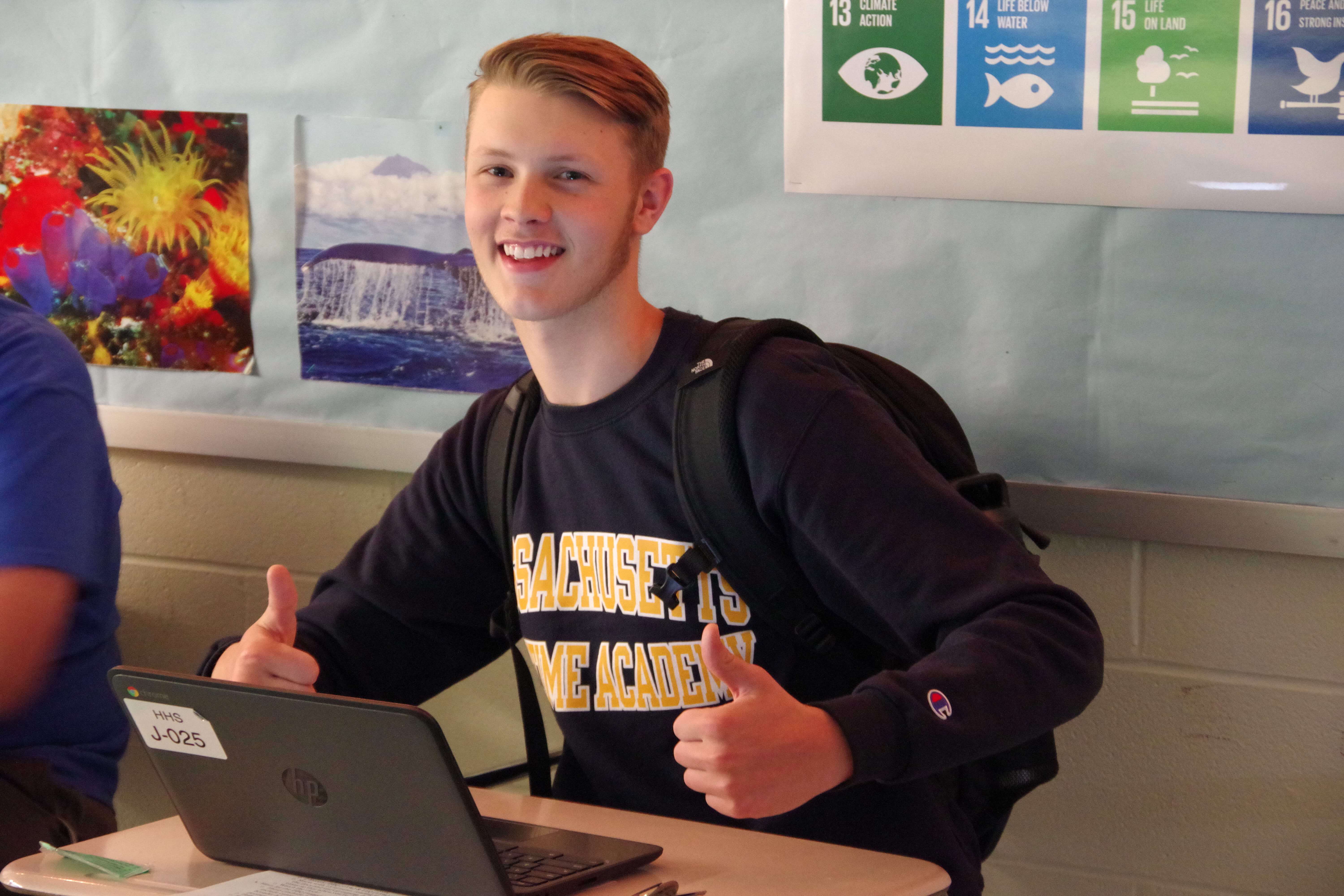 High school student excited to be in class, giving the thumbs up will sitting at his desk.