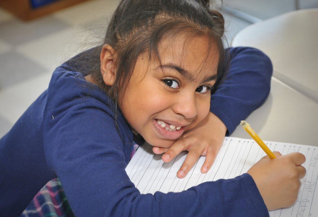 EN White Dual Language first grade female student sitting at desk with pencil and paper smiling in a purple shirt