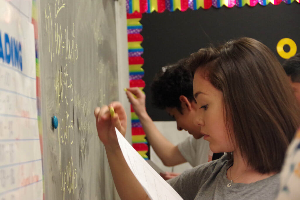 High school student working out a math equation at the chalk board.