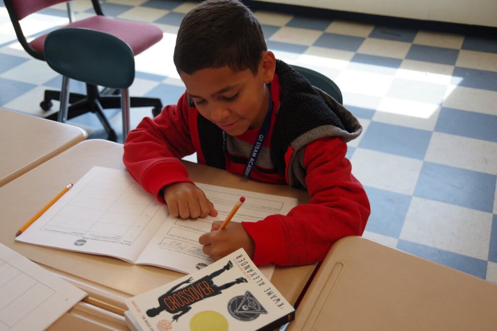 male student in red sweat shirt writing in a workbook at his desk