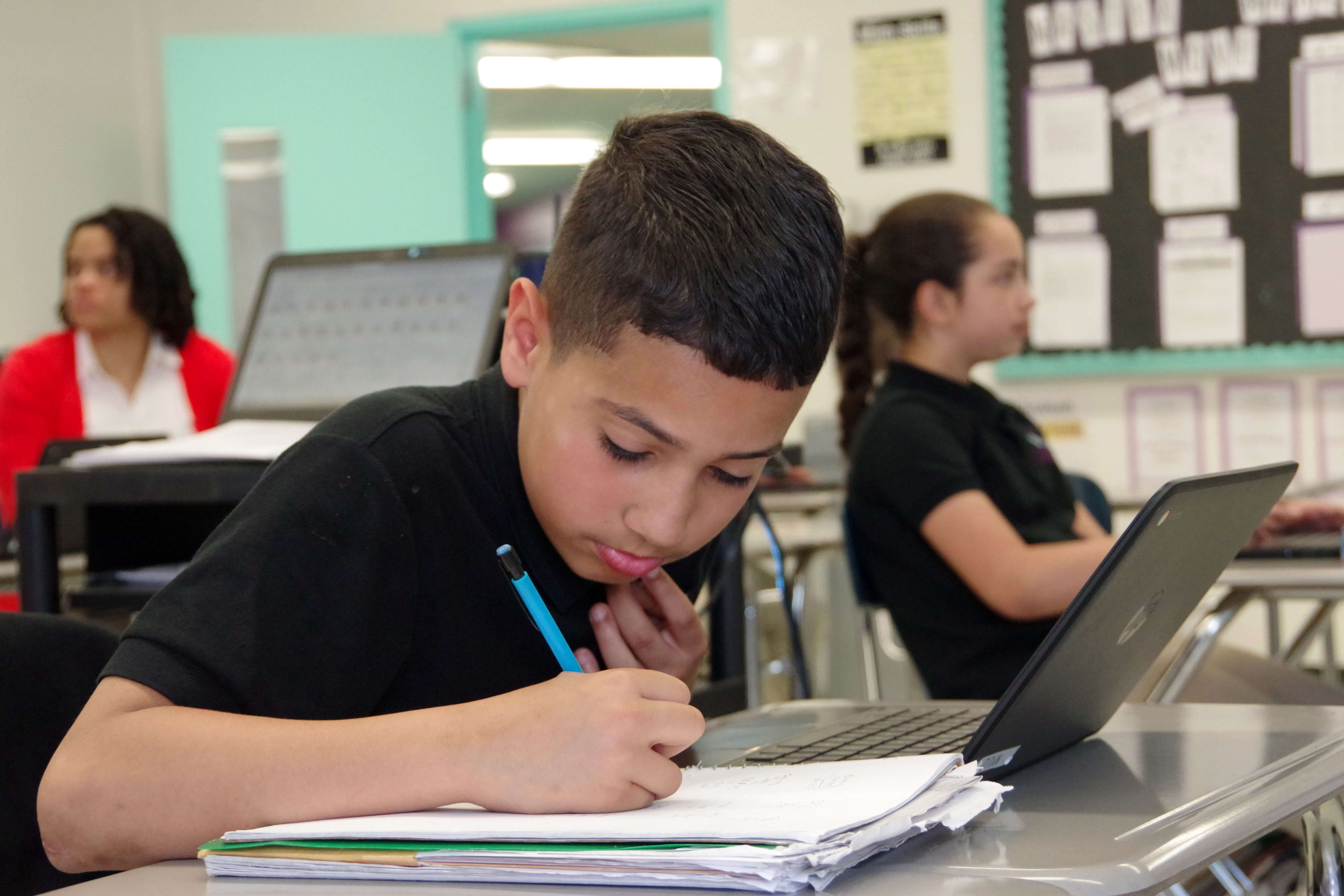 Middle school male student working on a class assignment.