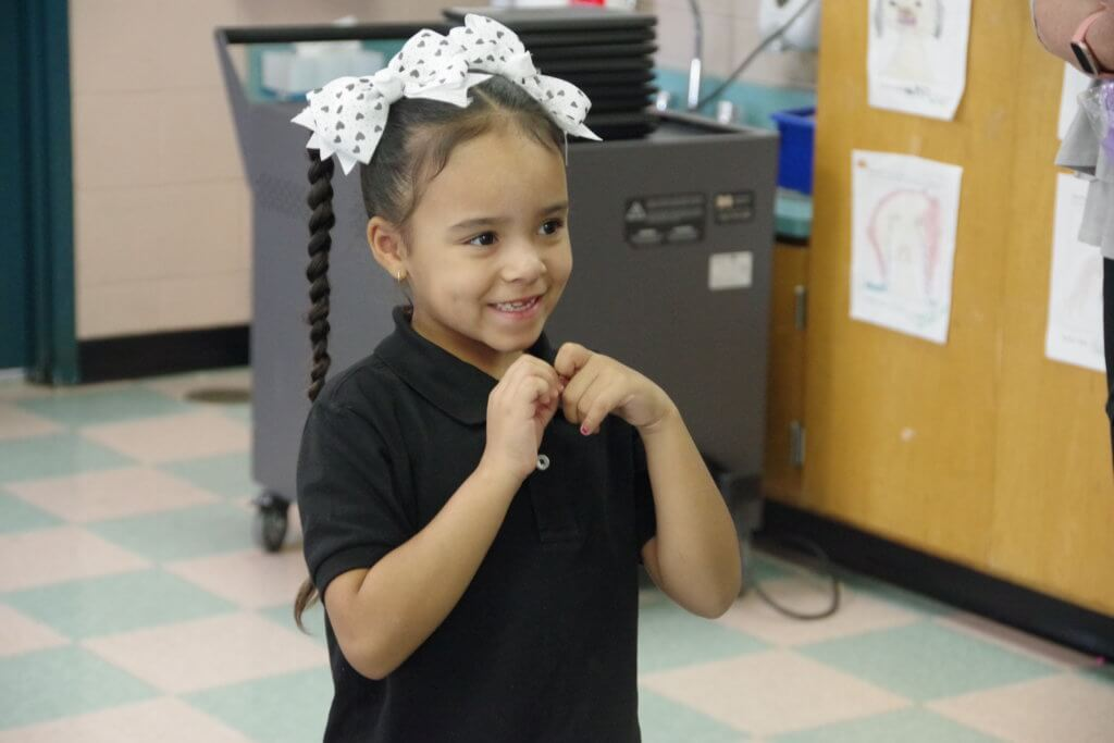 female student in black shirt with bow stands smiling