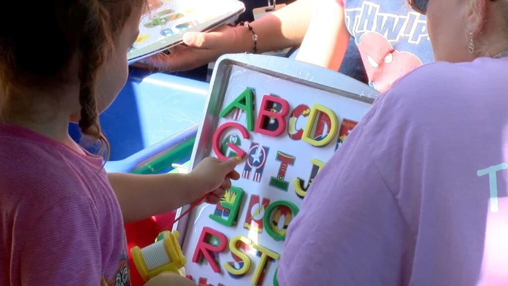 Preschool students are looking at capital letters that are on a tray.