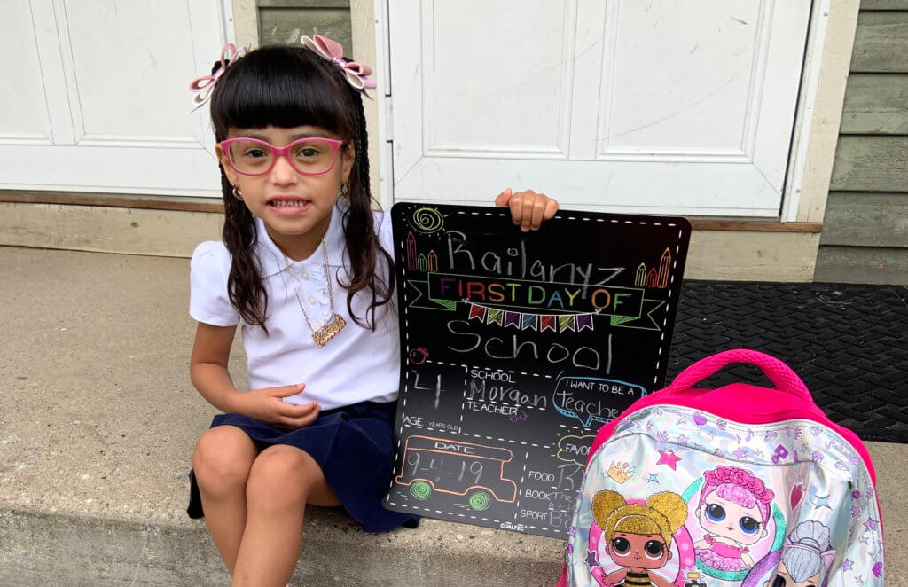Young female PreK student displays first day of school sign