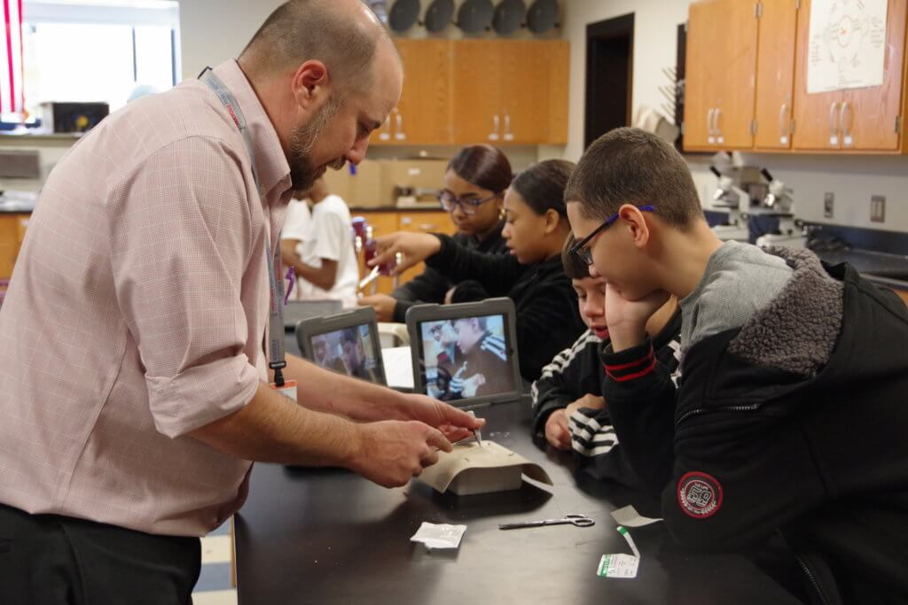 male teacher performing STEM activity with students