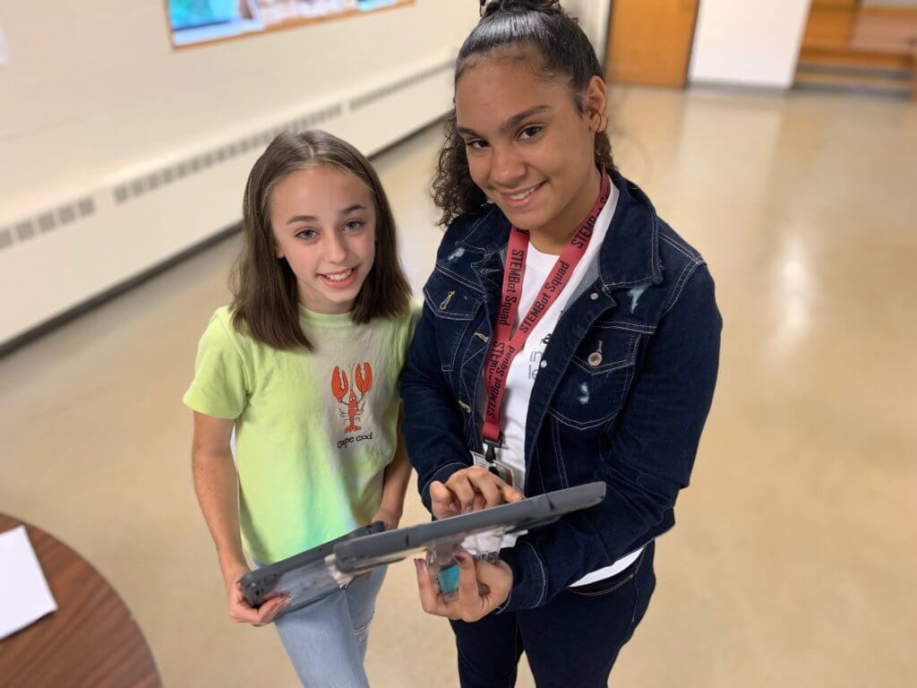2 female students standing next to each other holding an iPad