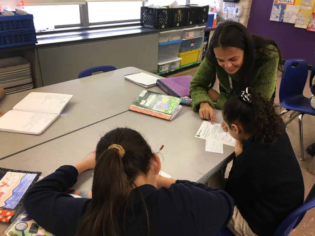 Rebecca Chaverri, McMahon School science teacher works at a table with 2 students