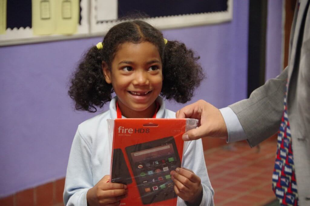 female elementary school student with pig tails smiles as she is handed a tablet prize