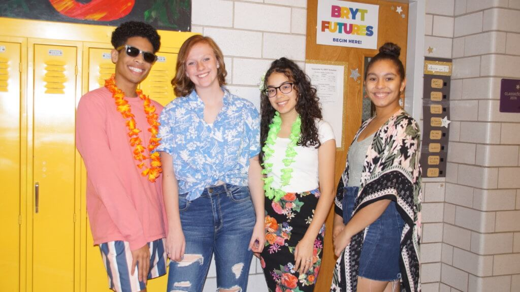 1 high school boy and 3 high school girls some with leis on standing in front of sign Bryt Futures sign