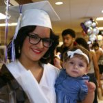 Female student at graduation holding a baby