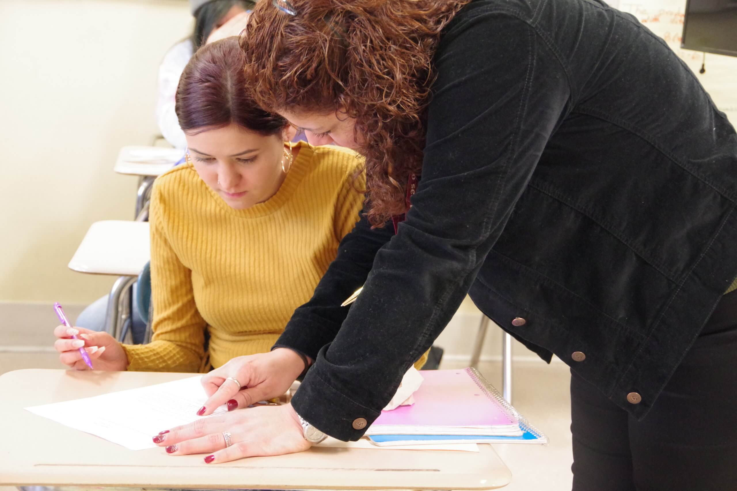 Female student working with a female teacher in class