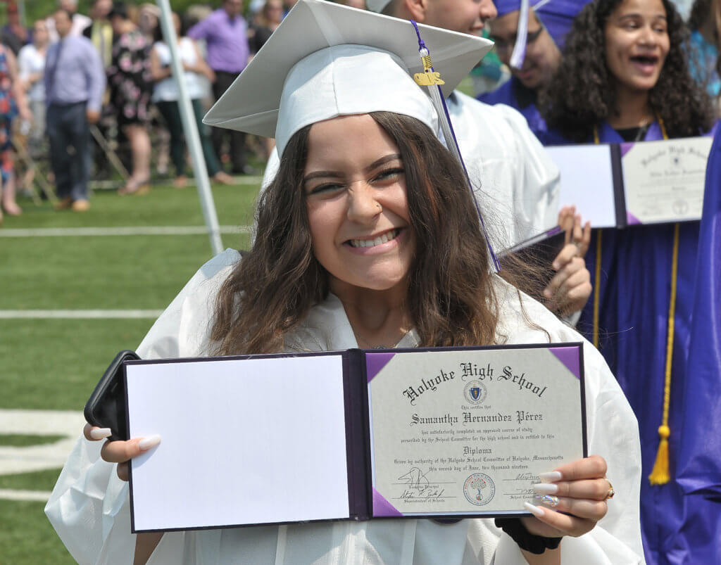 2019 female HHS graduate wearing white cap and gown smiles while holding diploma open