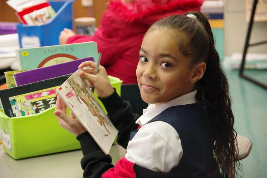 female elementary school student reading a picture book