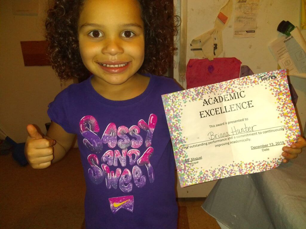 young student wearing purple sassy and sweet t-shirt holding academic excellence certificat