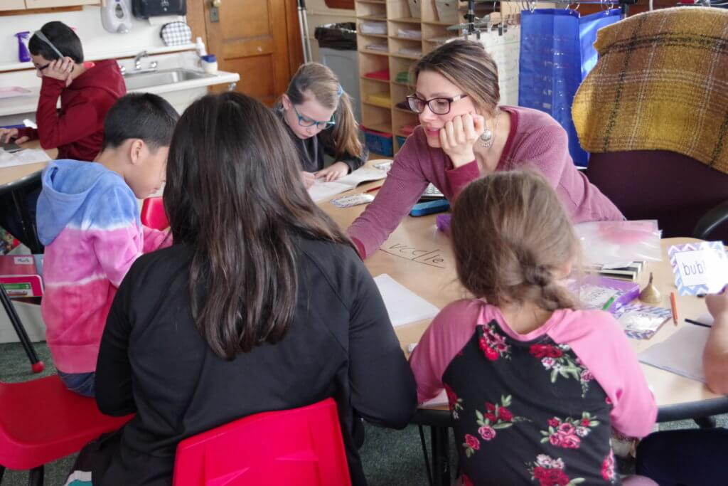 Metcalf teacher instructs group of students at small table