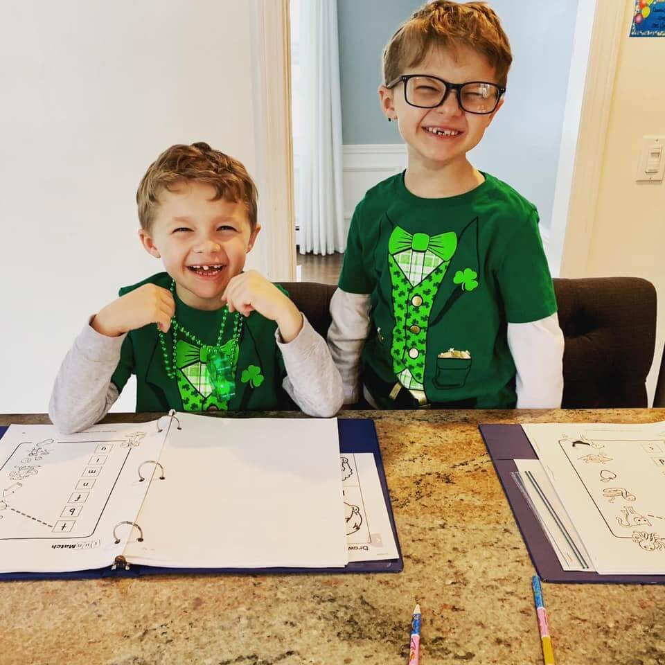 two boys wearing St. Pat's day shirts doing homework