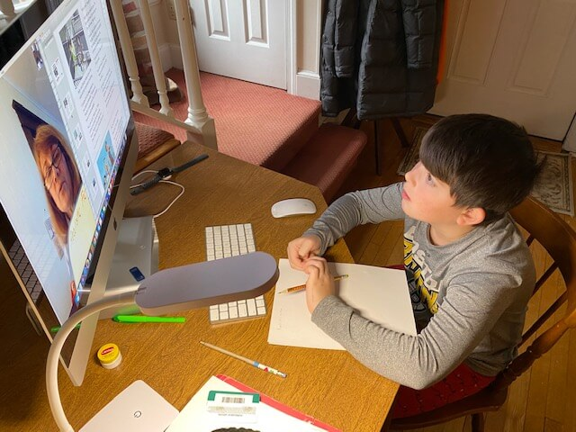 Male student at home learning seated at desk with computer