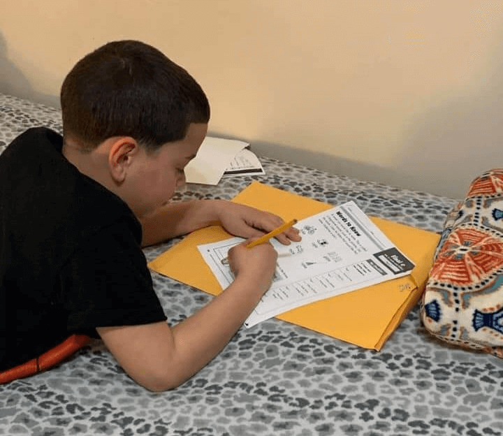 Young male student in black shirt lying on the floor while completing a worksheet that is on top of gold folder