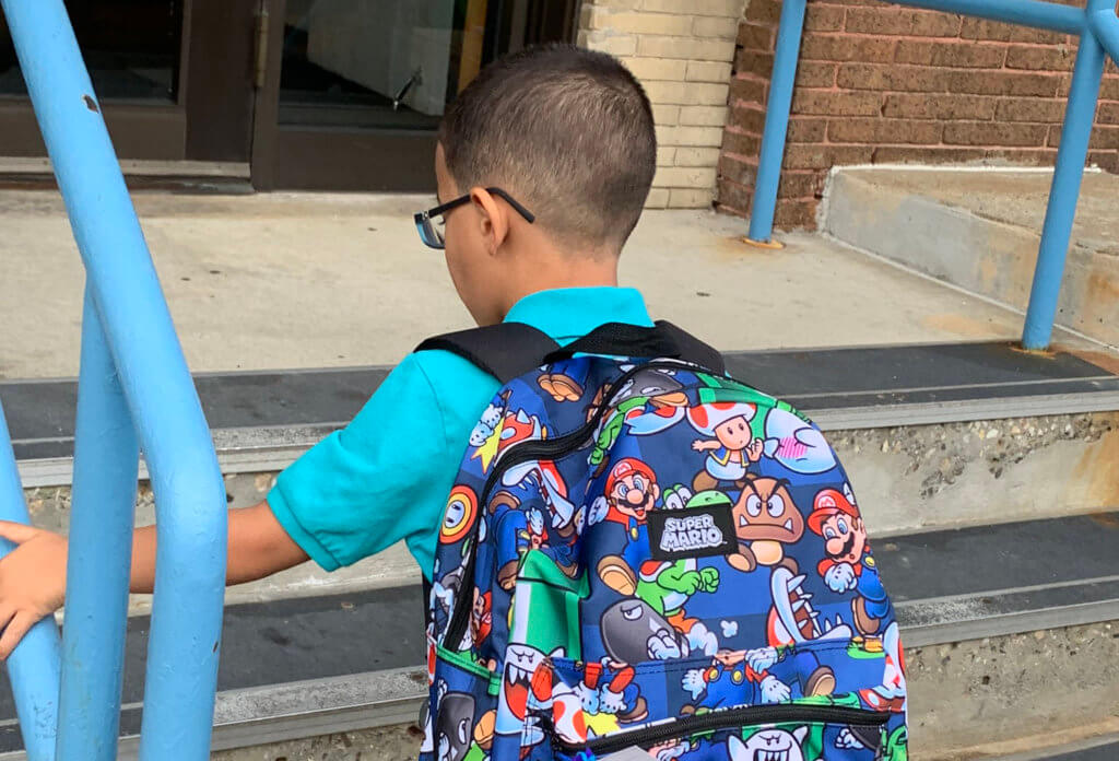 back to school boy walking into school with blue shirt glasses and mario backpack