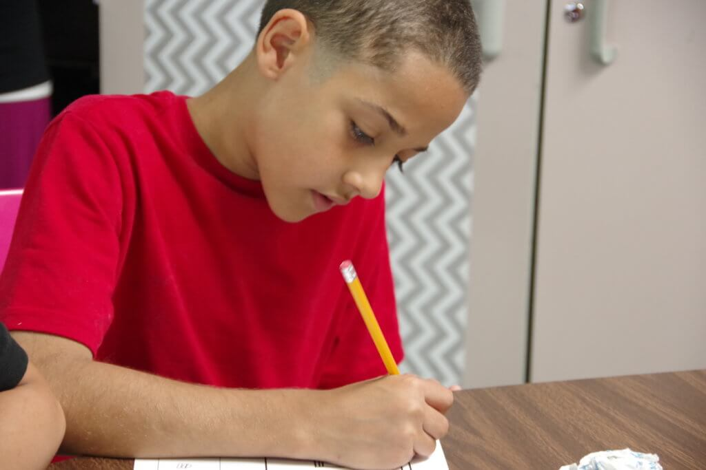 male student seated at desk with a pencil wearing a red tshirt