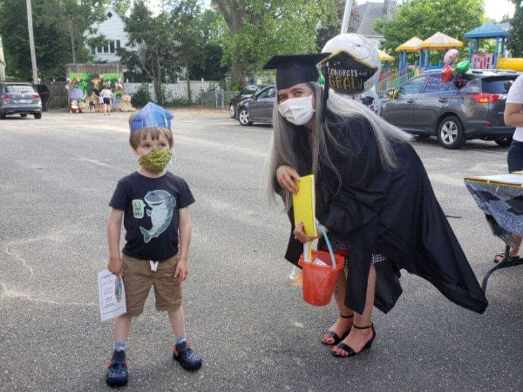 female adult in graduation cap and gown with young male student wearing a crown and child with mask 8-27-20 holyoke Update