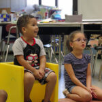 Two preschool students engaged in circle time.
